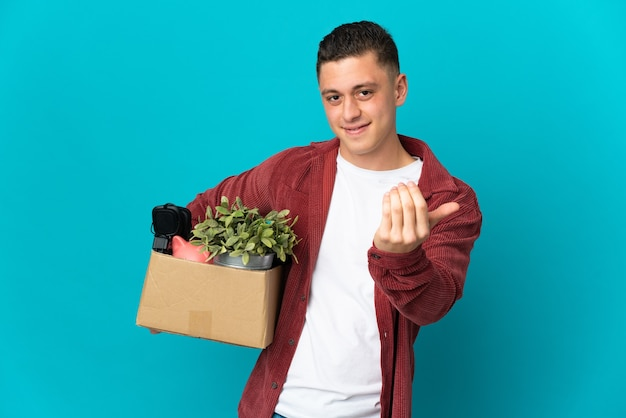 Young caucasian man making a move while picking up a box full of things isolated on blue inviting to come with hand. happy that you came