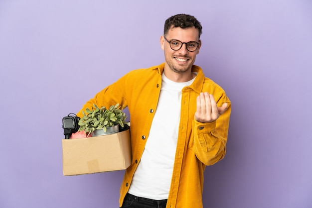 Young caucasian man making a move while picking up a box full of things isolated on purple inviting to come with hand. happy that you came