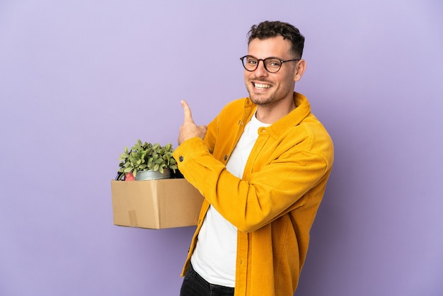 Young caucasian man making a move while picking up a box full of things isolated on purple pointing back