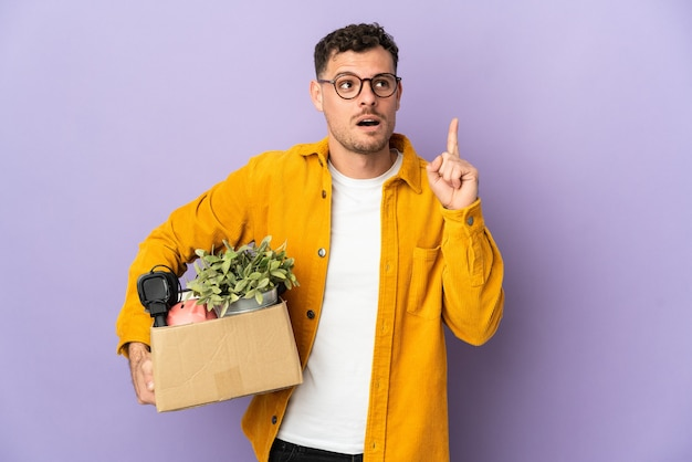 Young caucasian man making a move while picking up a box full of things isolated on purple thinking an idea pointing the finger up