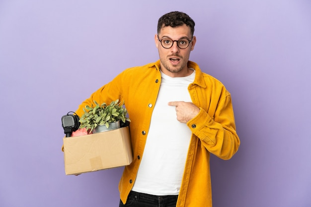 Young caucasian man making a move while picking up a box full of things isolated on purple wall with surprise facial expression