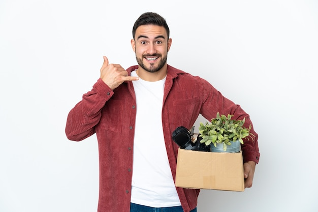 Young caucasian man making a move while picking up a box full of things isolated on white wall making phone gesture. call me back sign