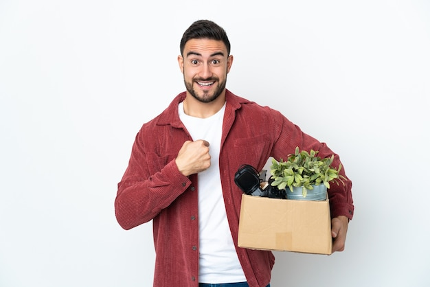 Young caucasian man making a move while picking up a box full of things isolated on white wall with surprise facial expression