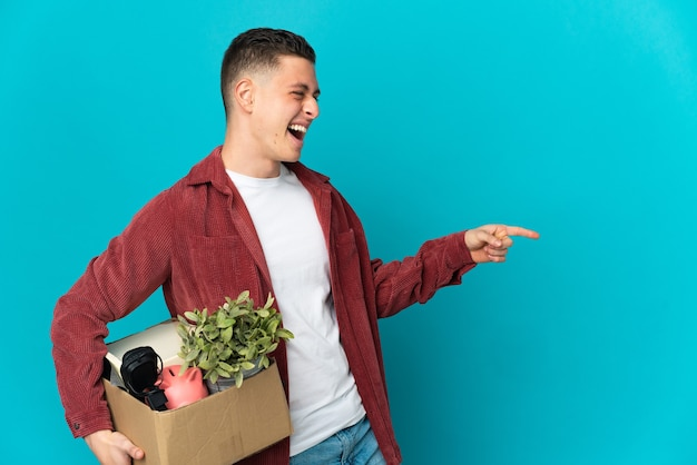 Young caucasian man making a move while picking up a box full of things isolated