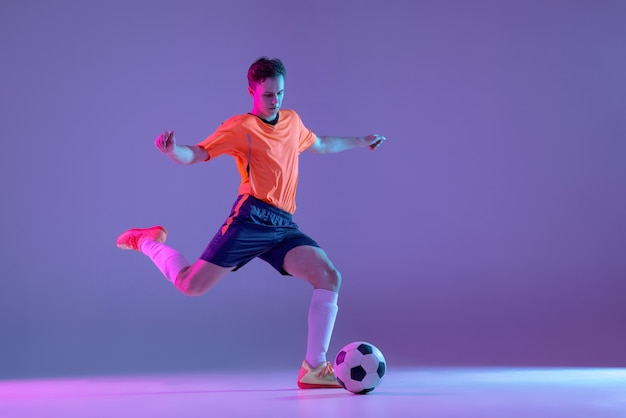 Young caucasian man male soccer football player training isolated on gradient blue pink wall in neon light