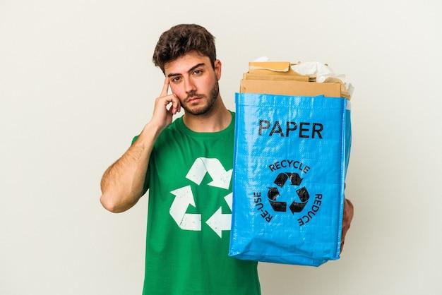 Молодой человек кавказской, рециркулирующий картон, изолированный на белом фоне, указывая храм пальцем, думая, сосредоточился на задаче.