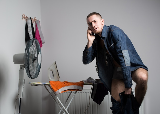 Young caucasian man model in grey underpants standing opposite fan and ironing his underwear over grey wall background.