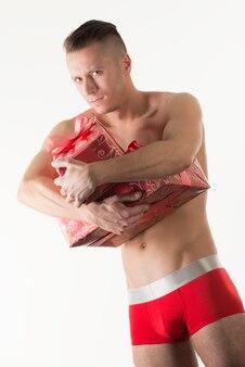 서서 사진 스튜디오에서 밝은 배경 위에 손에 선물 상자를 들고 빨간 망 속옷에 젊은 백인 남자 모델. 밝은 남성 속옷 컨셉