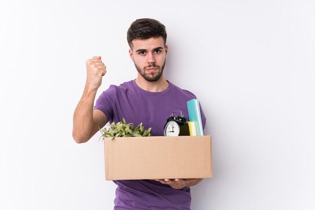 Молодой кавказский человек, перемещающий новый дом, изолировал, показывая кулак, агрессивное выражение лица.