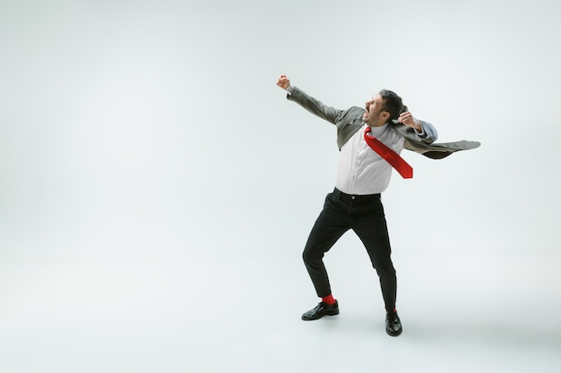 Young caucasian man moving flexible on white  wall. male model in office attire bending over, avoiding something, catched in motion and action. looks angry, scared, fighting. emotions.