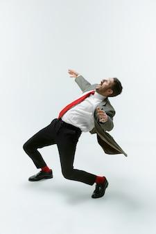 Giovane uomo caucasico che si muove flessibile sul muro bianco