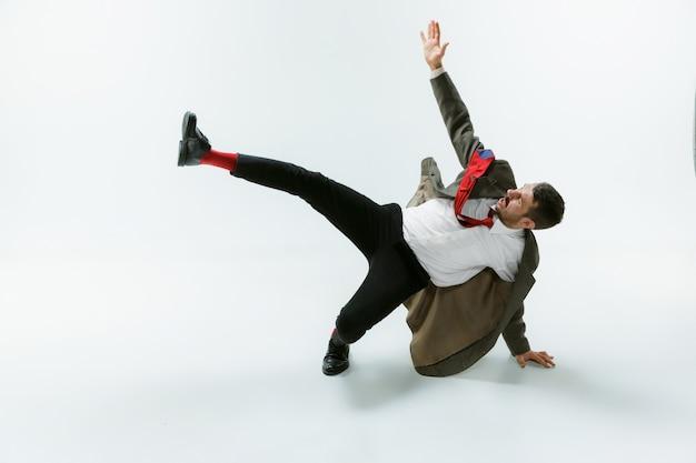 Giovane uomo caucasico che si muove flessibile su bianco