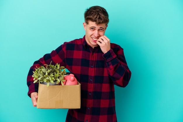 Молодой кавказский человек движется, держа коробку, изолированную на синей стене, кусая ногти, нервничает и очень тревожится.