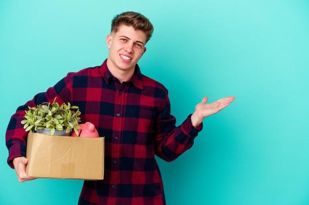 手のひらにコピースペースを示す青い壁に隔離されたボックスを保持し、腰に別の手を保持して移動する若い白人男性。