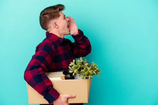 Young caucasian man moving holding a box on blue shouting and holding palm near opened mouth.