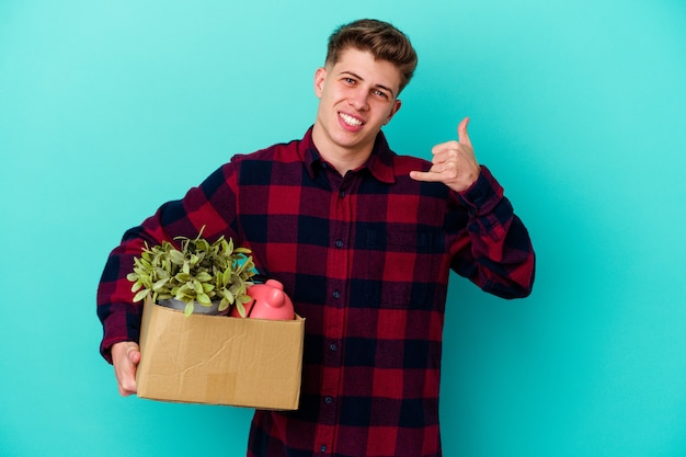Young caucasian man moving holding a box on blue showing a mobile phone call gesture with fingers.