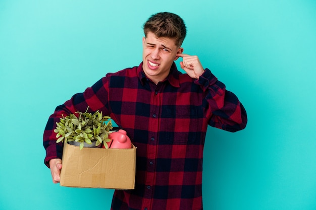 Young caucasian man moving holding a box isolated on blue wall covering ears with hands.