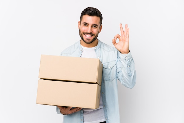 Young caucasian man moving to a new home isolated cheerful and confident showing ok gesture.