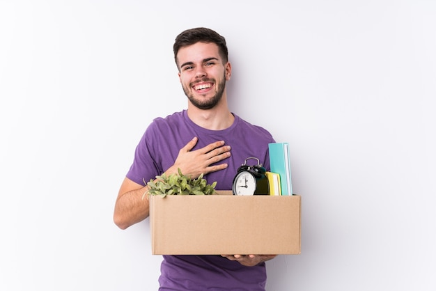 Young caucasian man moving a new home isolated laughs out loudly keeping hand on chest.