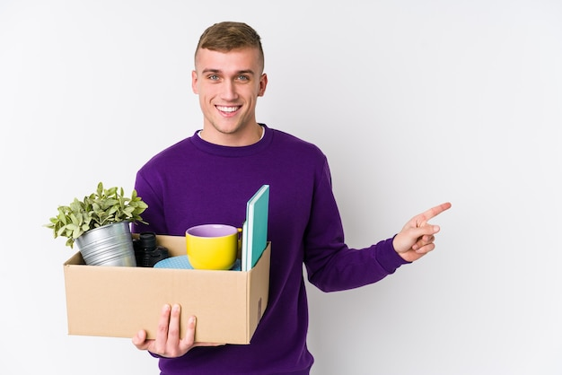 Young caucasian man moving to a new home smiling and pointing aside, showing something at blank space.