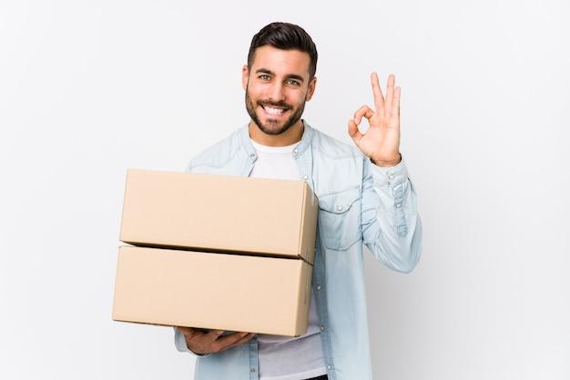 新しい白人の若者が新しい家に移動すると、明るく自信を持ってokのしぐさを示します。