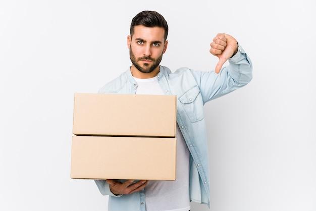 Молодой кавказский человек, переезжающий в новый дом, изолированные, показывая жест неприязни, пальцы вниз. концепция несогласия.