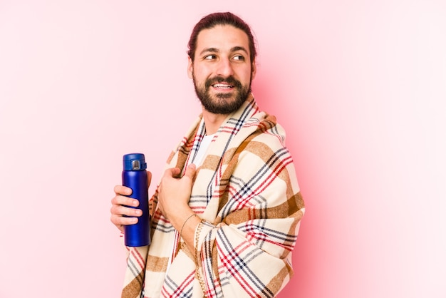 Молодой кавказский мужчина в походный день с термосом смотрит в сторону улыбающимся, веселым и приятным.