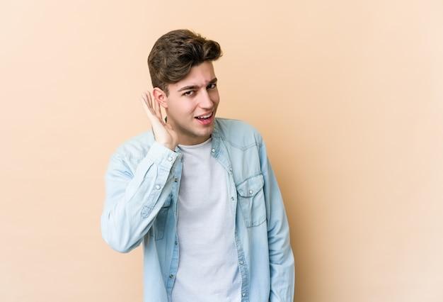 Молодой кавказский человек на бежевой стене пытается слушать сплетни.