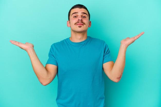 파란색 혼란과 의심스러운 shrugging 어깨에 젊은 백인 남자 복사본 공간을 유지합니다.