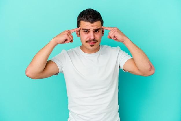 파란색에 젊은 백인 남자는 머리를 가리키는 집게 손가락을 유지하는 작업에 집중했습니다.