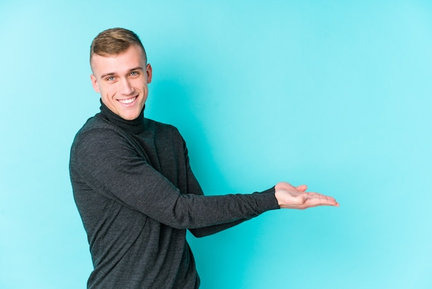 手のひらにコピースペースを保持している青の若い白人男。