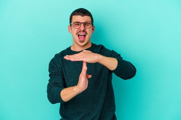 Молодой кавказский человек на синем, показывая жест тайм-аута.