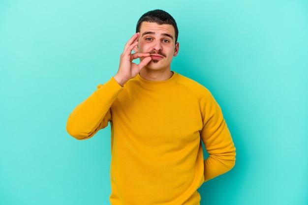 秘密を守っている唇に指を持った青の若い白人男性。