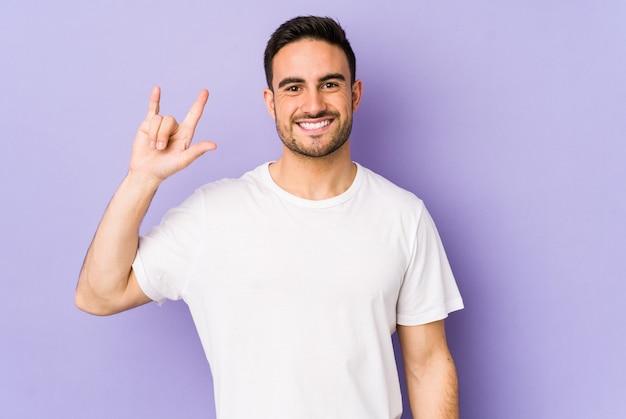 革命の概念として角のジェスチャーを示す紫色の若い白人男性。