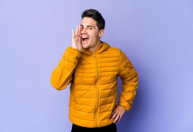 Молодой кавказский человек на фиолетовой стене кричит