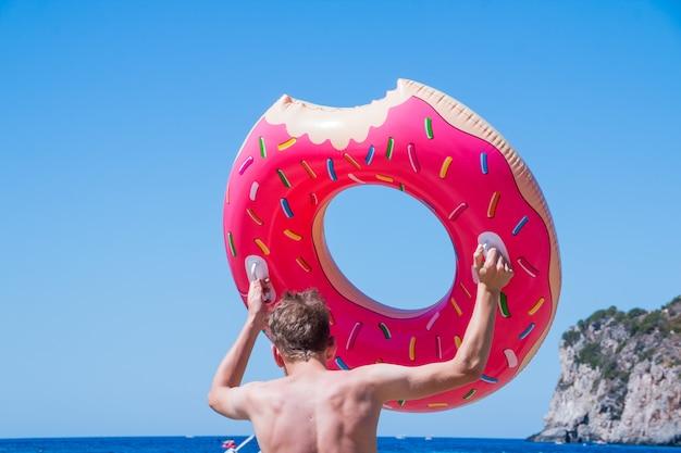 大きなドーナツの形をした水泳リングとビーチで若い白人男