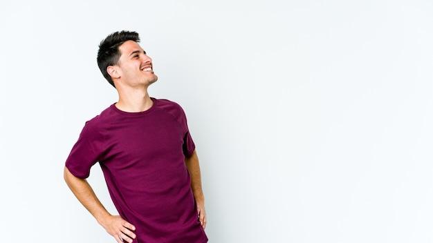Молодой кавказский человек на белом расслабленным и счастливым смехом, вытянув шею, показывая зубы.