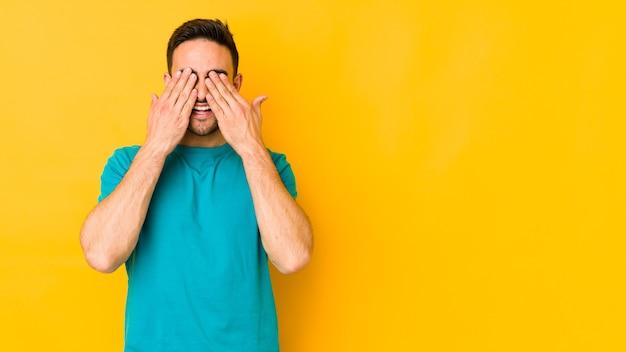 노란색 bakground에 젊은 백인 남자는 놀라움을 광범위하게 기다리고 미소 손으로 눈을 다룹니다.