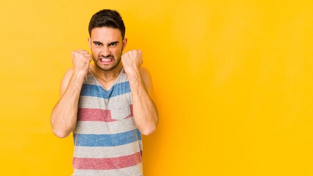 주먹, 공격적인 표정을 보여주는 노란색 bakground에 젊은 백인 남자.