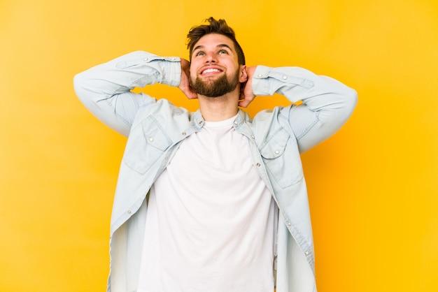 頭の後ろに手で自信を持って、黄色の壁に若い白人男。