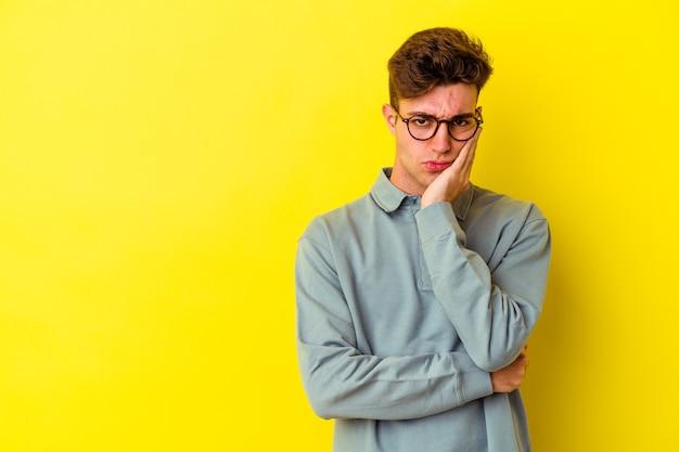 Молодой кавказский человек на желтом, который чувствует себя грустно и задумчиво, глядя на пространство для копирования.