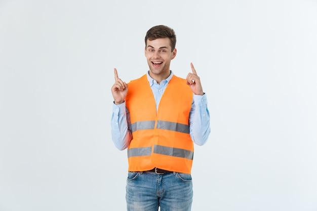 請負業者の制服と安全ヘルメットを身に着けている白い背景の上の若い白人男性は、幸せそうな顔で指を指すアイデアや質問に驚いた、ナンバーワン。