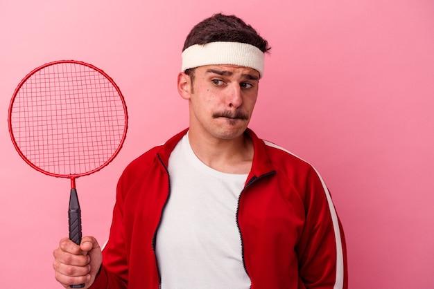 Молодой кавказский человек играет в бадминтон на розовом фоне в замешательстве, чувствует себя сомнительным и неуверенным.