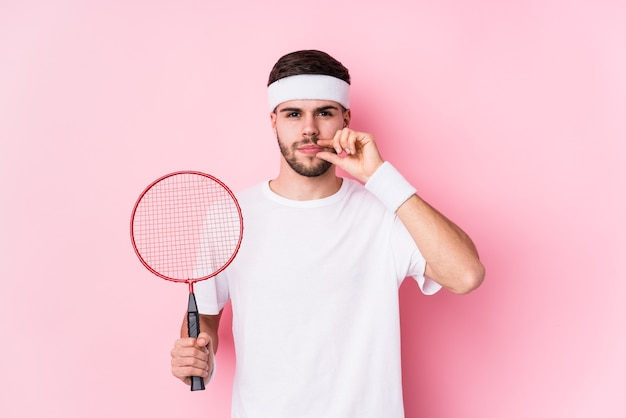 Young caucasian man playing badminton isolated with fingers on lips keeping a secret.