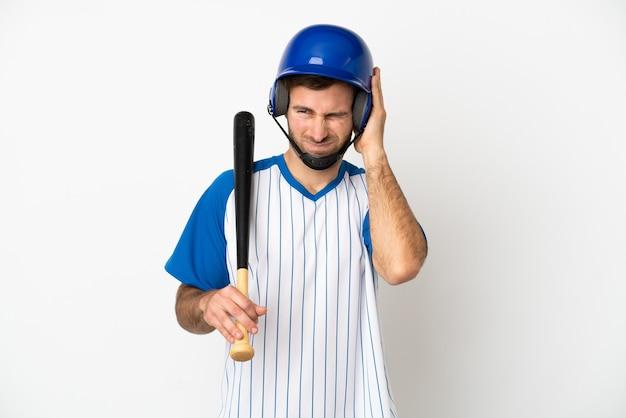 Молодой кавказский человек играет в бейсбол на белом фоне разочарован и закрывает уши