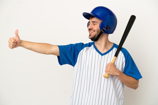 Молодой кавказский мужчина играет в бейсбол, изолированные на белом фоне, показывает жест рукой вверх