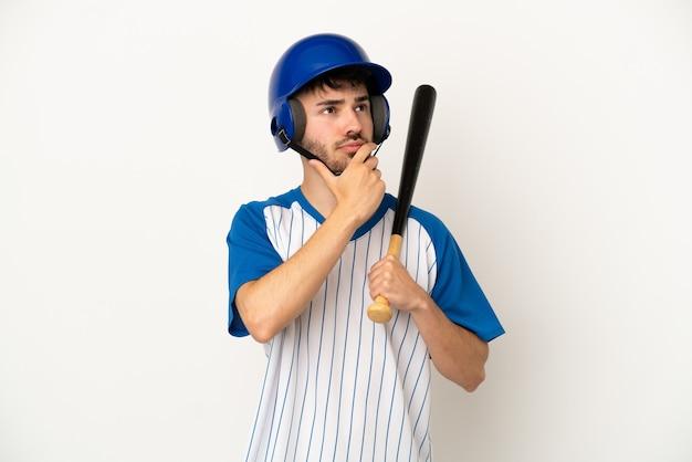 Молодой кавказский человек играет в бейсбол на белом фоне, сомневаясь