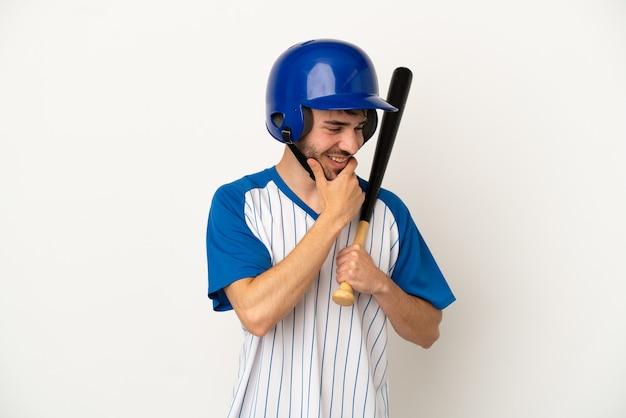 Молодой кавказский человек играет в бейсбол на белом фоне, глядя в сторону и улыбается