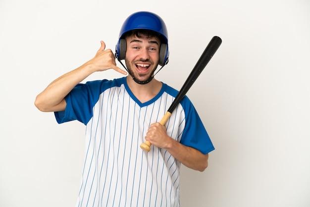 Молодой кавказский человек играет в бейсбол на белом фоне, делая телефонный жест. перезвони мне знак
