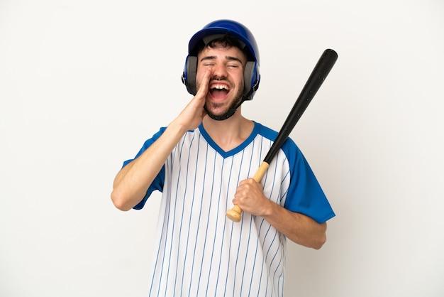 Молодой кавказский мужчина играет в бейсбол на белом фоне и кричит с широко открытым ртом